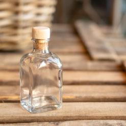 Botellita de vidrio vacía Amaya con corcho de madera